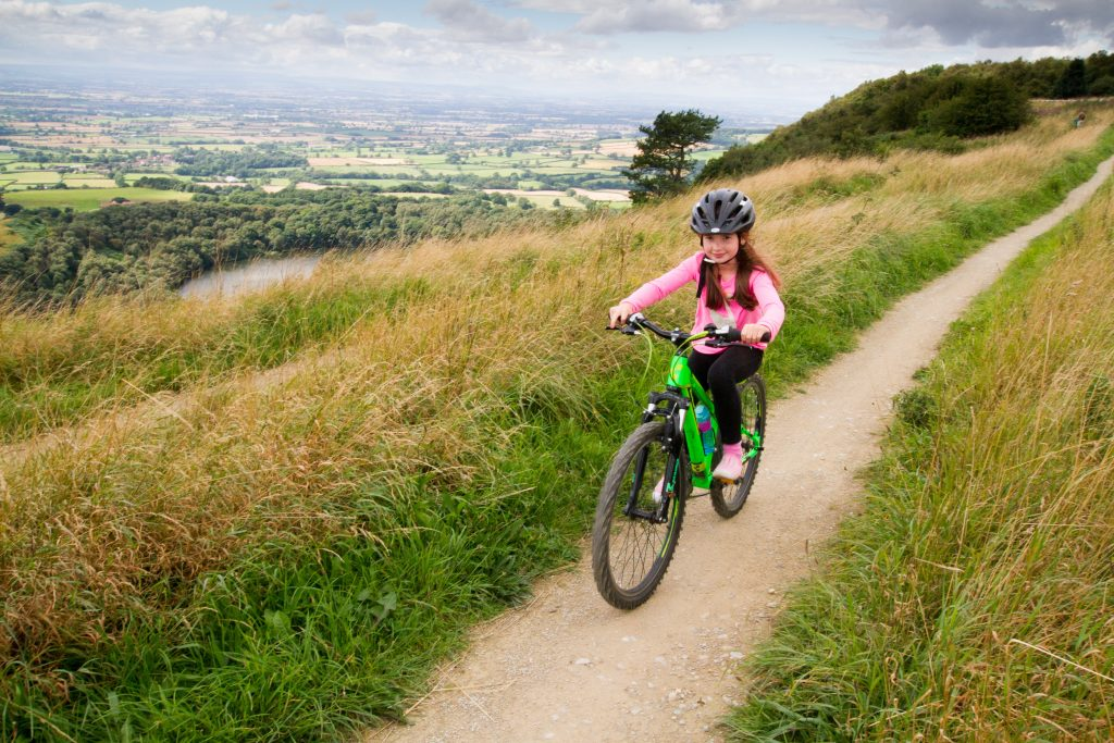 Image of young girl on bike, cycling on a hillside trail in Ryedale