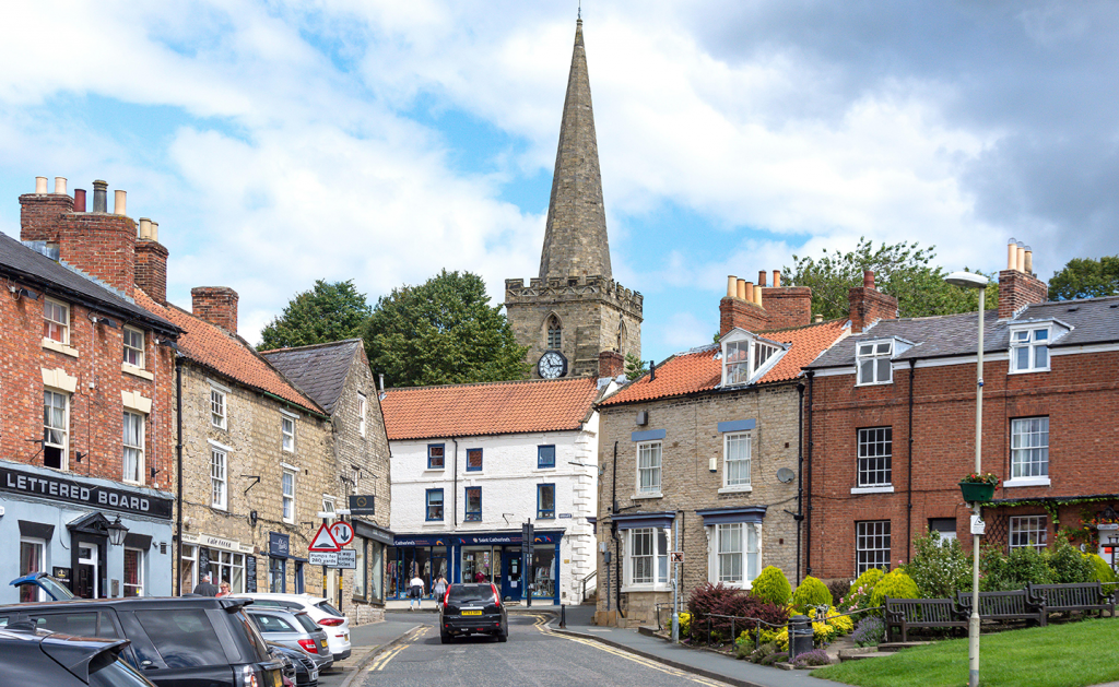 Picture of the centre of Pickering with old buildings and a church spire in the background
