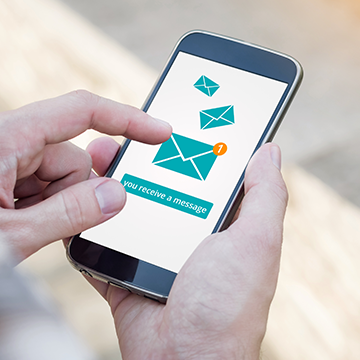 Picture showing a person's hands holding a mobile phone with a newsletter icon on the screen.